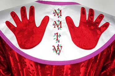 close up of red jingle dress showing two bright red hands on a white yoke with the letters MMIW embroidered down the center