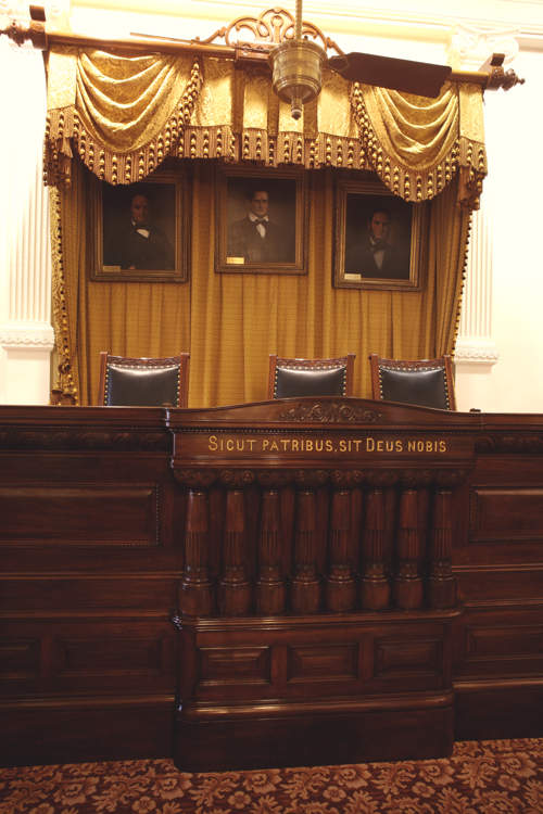 "Original Supreme Court judges' bench. The Latin phrase reads, ""As to our fathers, may God be to us."""