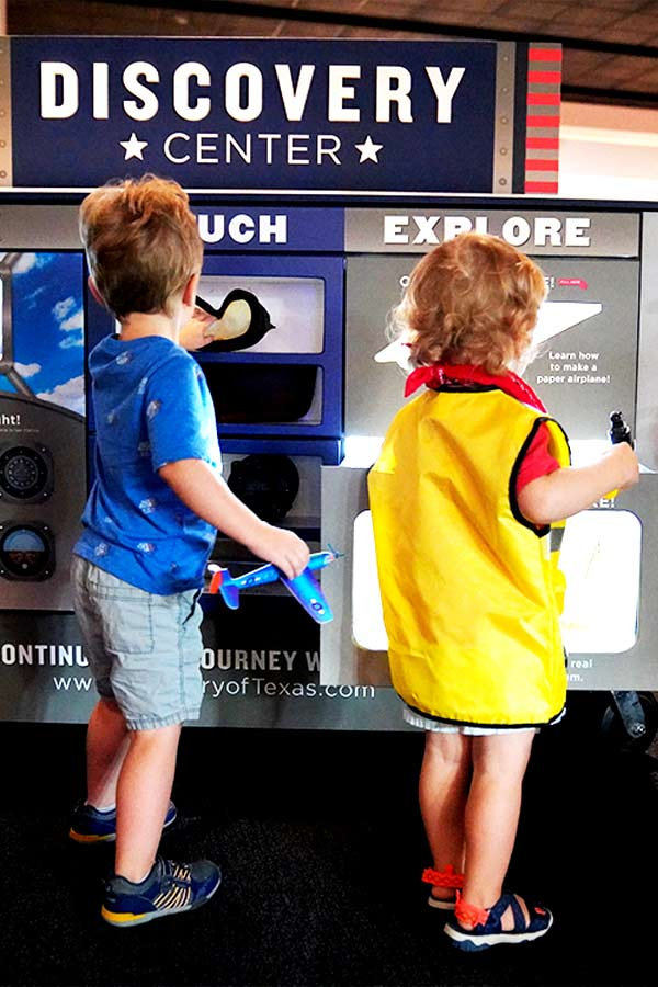 Two children interacting with space exhibit