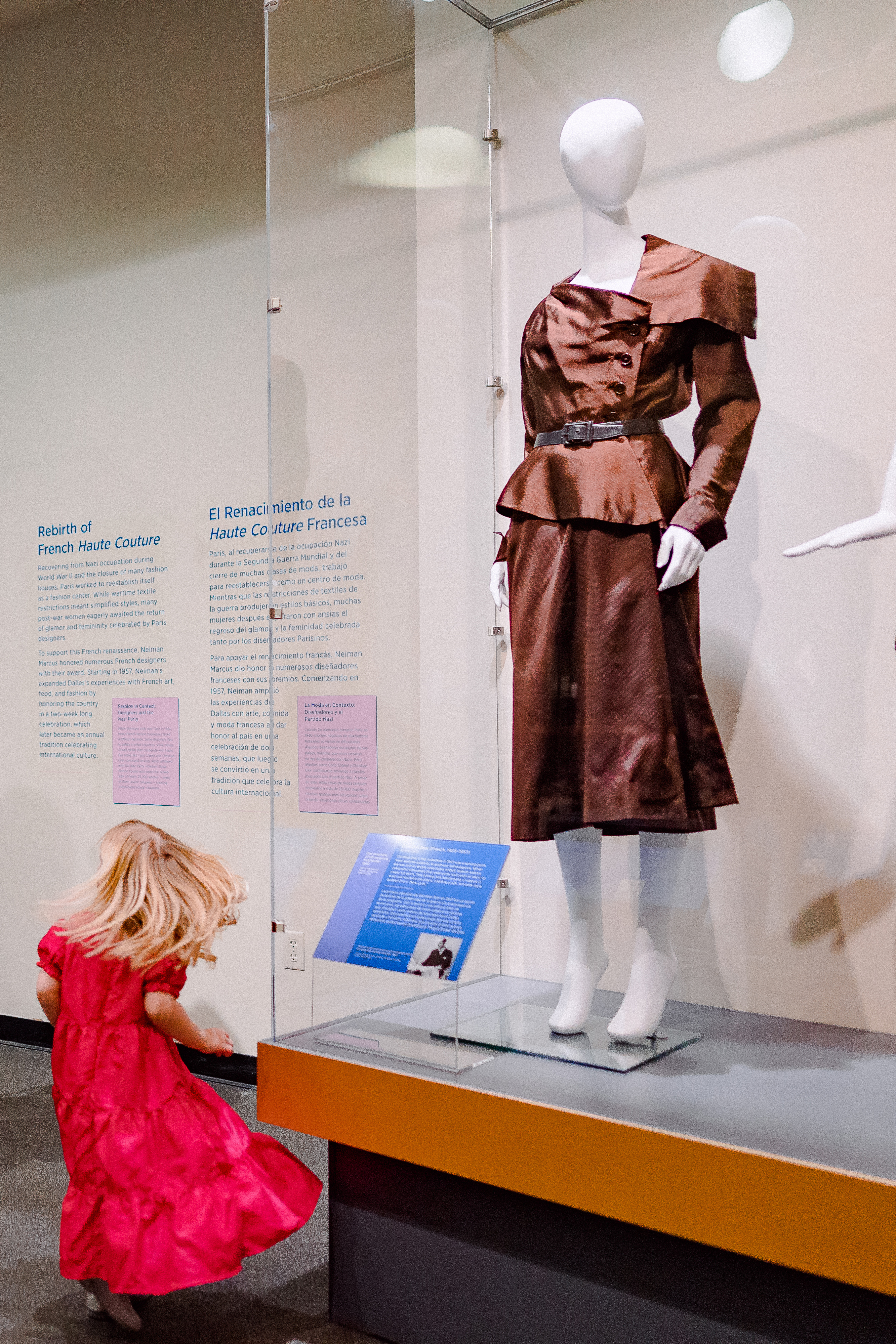 Young girl in front of mannequin at Fashion Forward Exhibit