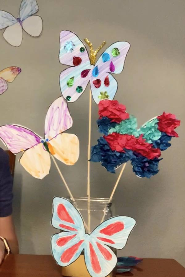 Three colorful paper butterflies on sticks in a vase