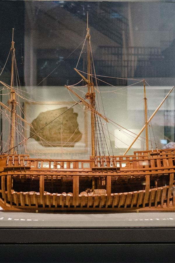 wooden model of the ship La Belle with the cargo section open showing barrels and rope
