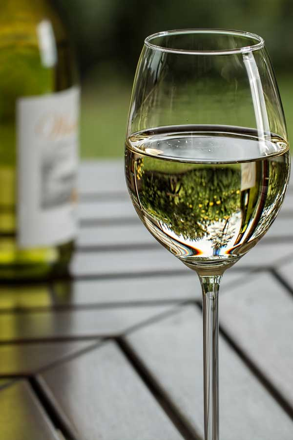 Glass of white wine on a wooden table outdoors