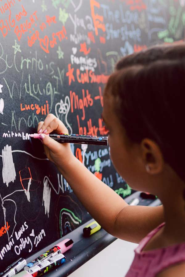 Close up of child drawing on a black chalkboard