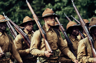 marching men in brown soldier uniforms, holding rifles on their shoulders
