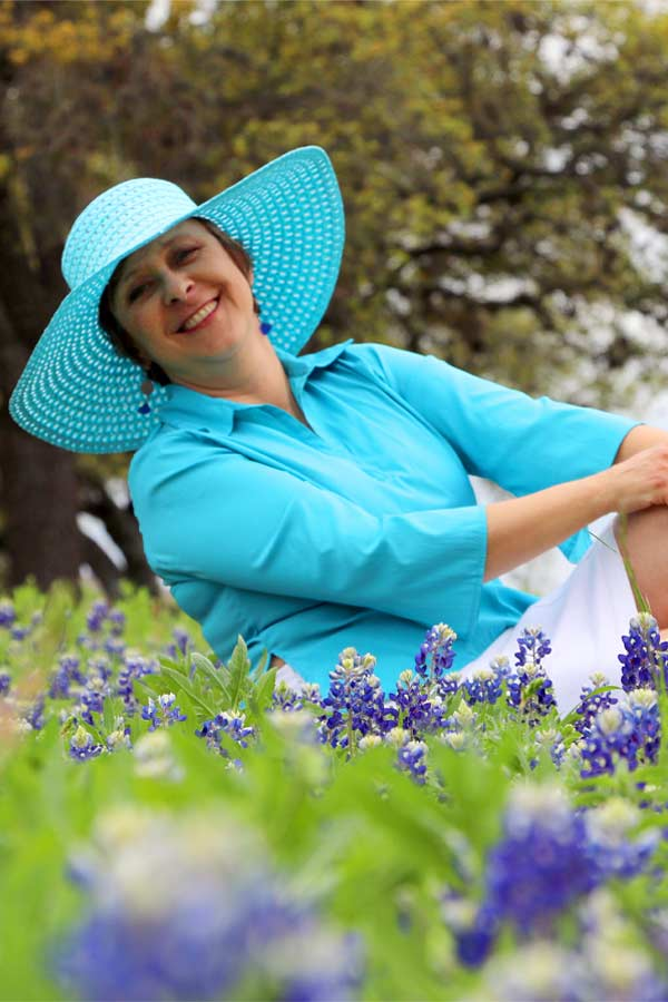 Woman posing as Ladybird Johnson wearing blue outfit and blue sun hat, sitting in a field of blue bonnet flowers