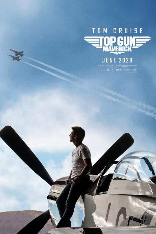 Tom Cruise as Maverick, leaning against a jet plane, looking up at two jets in a blue sky