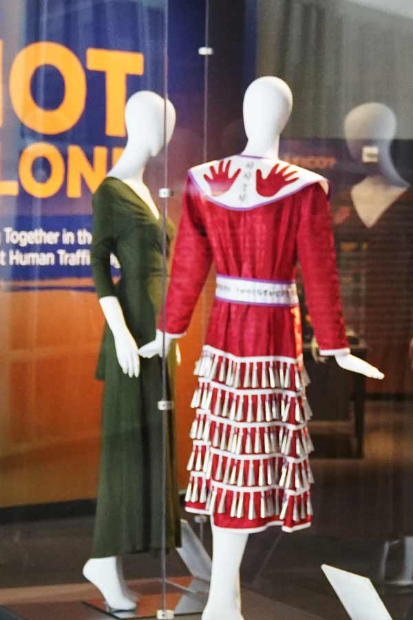 a museum display case containing two mannequins, one wearing a green Dressember dress and the other wearing a Red Jingle Dress by Nan Blassingame