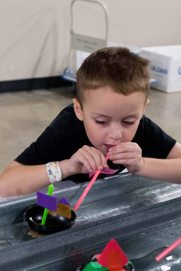 young boy blowing through a straw to make a paper boat move
