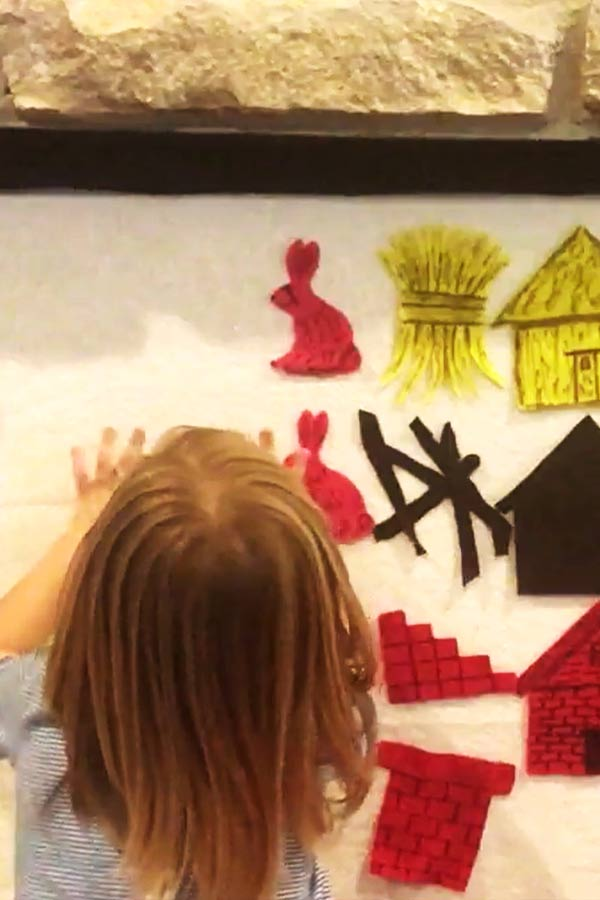 Young child placing a red rabbit on a white piece of paper on a wall. There are cut outs of bricks, a house, hay, and sticks also on the paper.