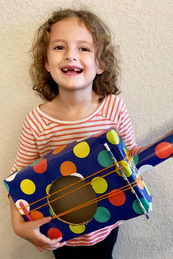 "child smiling and holding a ""guitar"" made out of cardboard and decorated with polka dots"