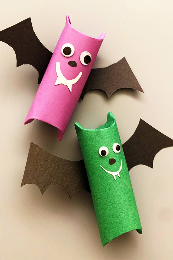 Two handmade craft bats made out of toilet paper rolls, one is pink and one is green