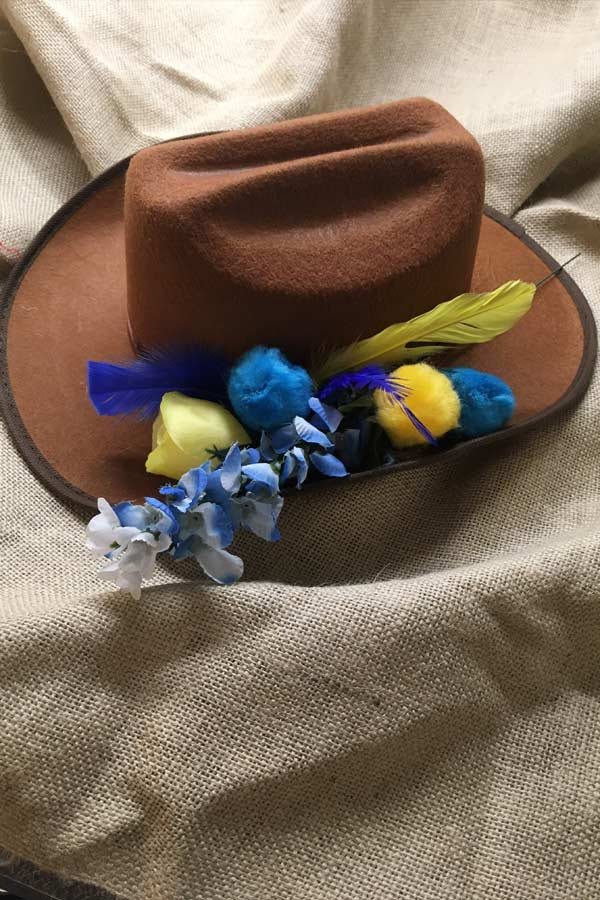 a brown cowboy hat decorated with yellow and blue flowers and feathers