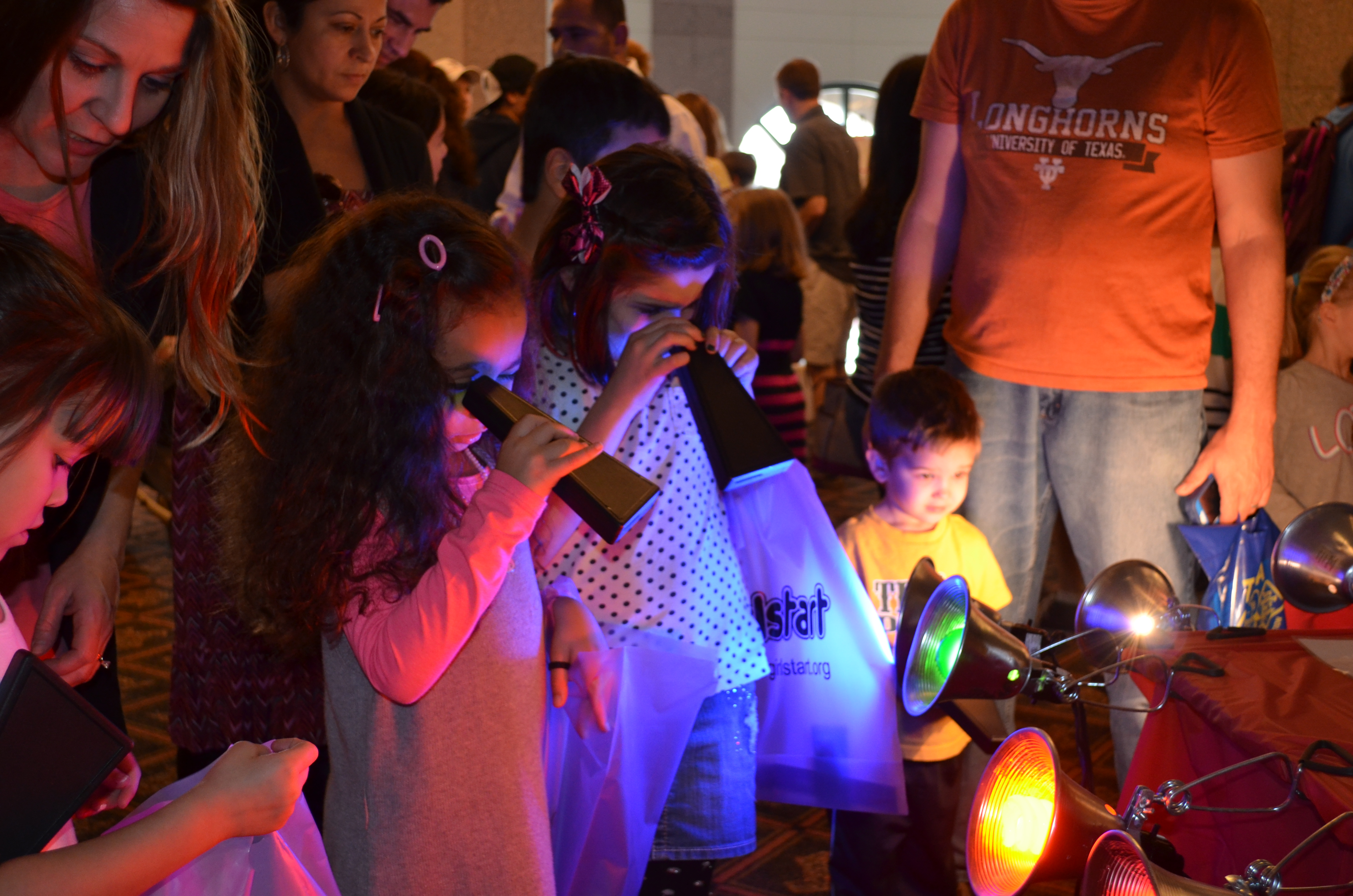 Young visitors explore the spectrum of different light sources with spectroscopes at the Bullock Museum's annual WeatherFest event.