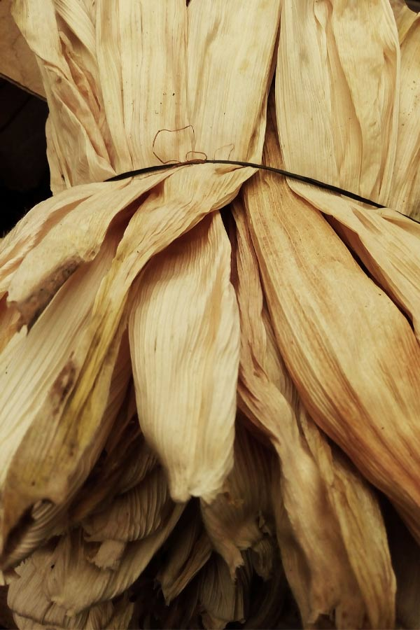 pile of dried corn husks on a black background