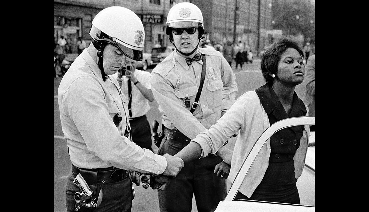 A picketer is arrested behind Loveman's Department Store. Civil rights leaders believed that if they could break segregation in Birmingham, it would collapse throughout the South. ©1963 Bob Adelman, Courtesy CDEA.