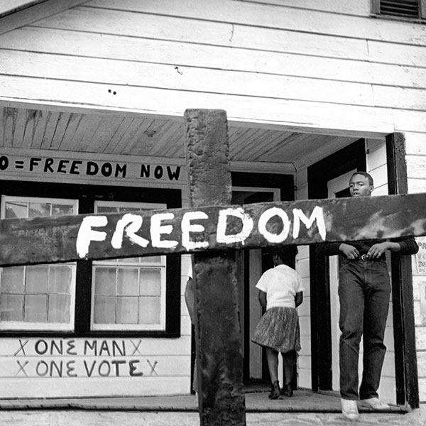 After the Ku Klux Klan burned this cross in front of a Mississippi Delta Freedom House, a civil rights worker transformed it with a painted message. Indianola, Mississippi. ©1964 Tamio Wakayama, Courtesy CDEA