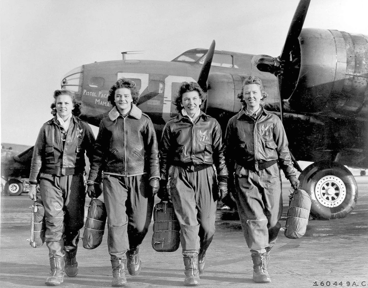 Four WASP pilots in flight gear and carrying parachutes with airplane in background