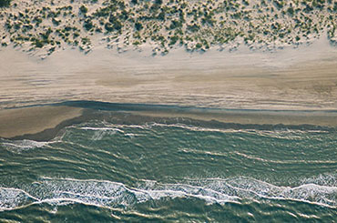 Texas beach from airplane view, blue waves crash on beige sand separated by a white line of foam