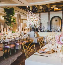 long tables in rows with gold chairs, in the center is a large pink and white floral centerpiece