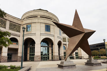 Outside of museum building with archways and a large brown lone star statue