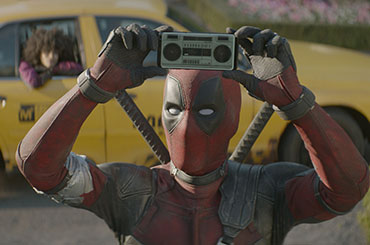 Still from Deadpool 2, Deadpool raises tiny boombox above head as a girl waits in a cab