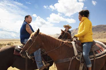 Three people on brown horses in a landscape with a mountain and blue skies