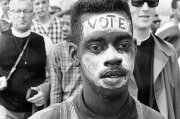 black and white close up photo of a man with the word VOTE painted on his forehead