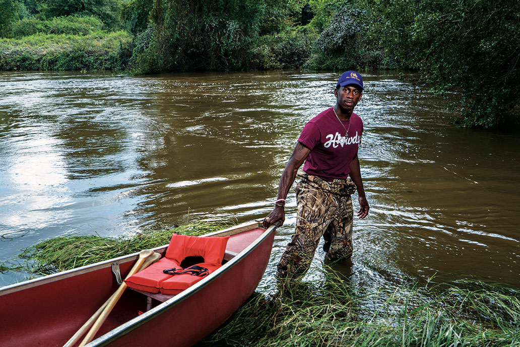Tyree Finley, whose story is featured in the exhibition, assists with flood rescue efforts. Courtesy of Darren Braun.