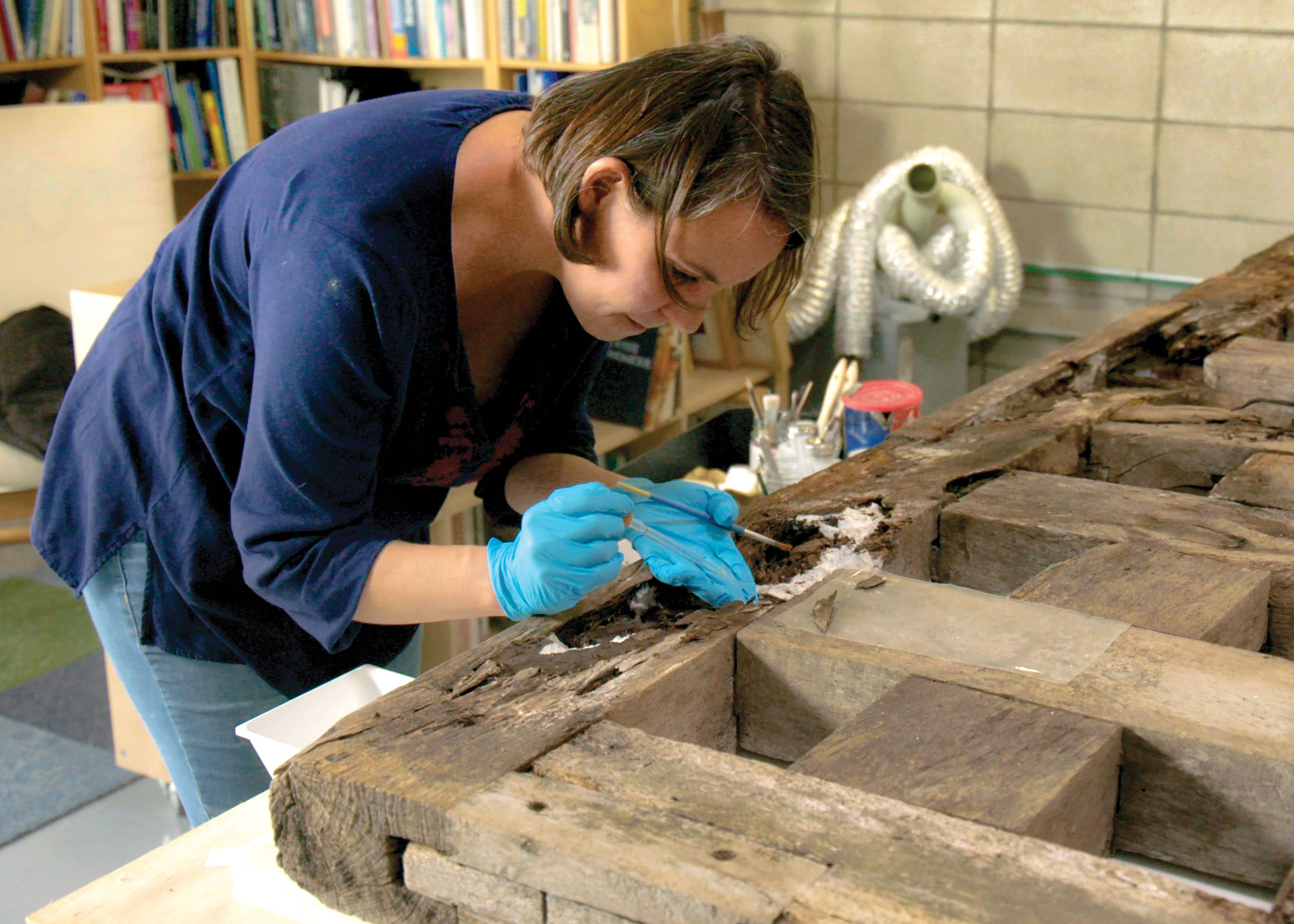 Conservator Catherine Williams utilized handmade paper to restore the damaged half of a rare Spanish mission gate, allowing it to be stable enough for display in Becoming Texas, opening December 10 at the Bullock Museum.